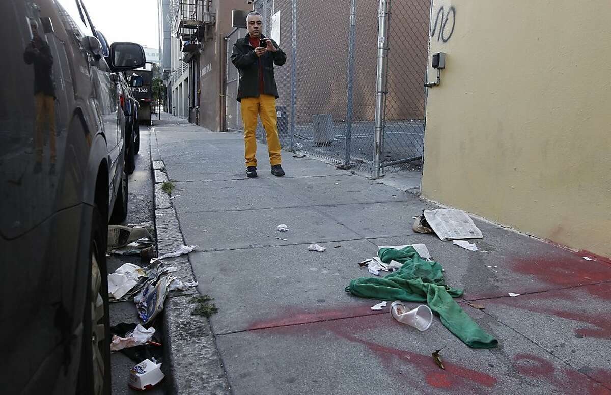Aman Jabbi records trash along Minna St. between 8th and 9th streets, in San Francisco, Calif. on Tuesday Oct. 22, 2012. The streets around Aman Jabbi's home on Minna Street is strewn with trash, feces and awash in urine. Jabbi recently started a tumblr FilthySF that records every aspect of the dirty street to pressure local officials into cleaning up the area.