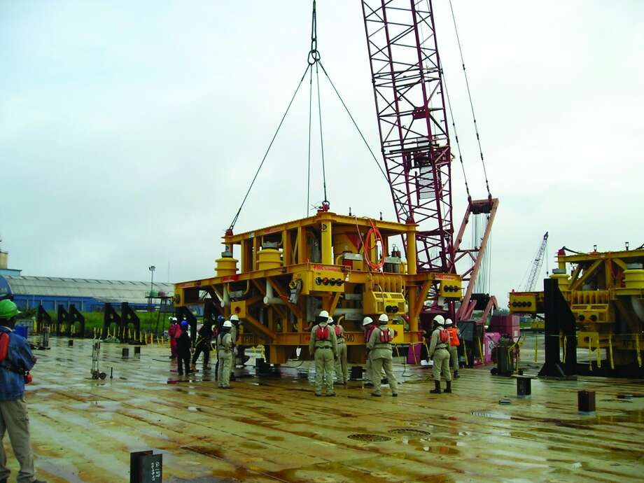 Workers handle an FMC Technologies enhanced horizontal subsea tree, subsea equipment that has been used for more than 150 well completions around the globe, including FMC's first major deepwater subsesa project in Nigeria. Photo: FMC Technologies