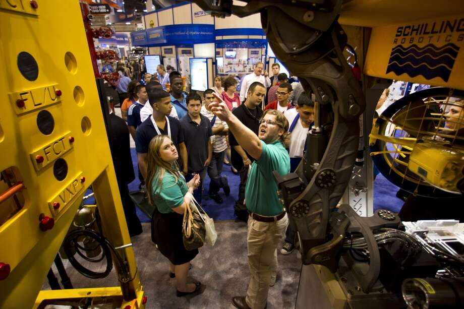 Matthew Vick (right) points to subsea equipment at the FMC Technologies booth as he gives a tour to high school students during the 2012 Offshore Technology Conference in Houston. Photo: Brett Coomer, Houston Chronicle