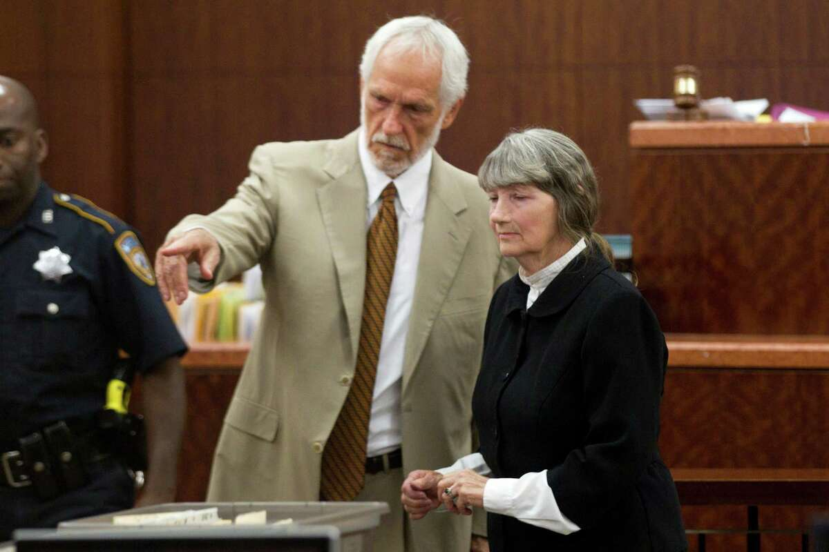 Attorney James Stafford, left, shows Carolyn Krizan-Wilson to her seat as she appears in court Wednesday, Oct. 23, 2013, in Houston. Krizan-Wilson pled guilty in the 1985 shooting death of her husband, Roy Joe McCaleb. The murder was a cold case for years. She was arrested in 2008. She was sentenced to 10 years probation and six months in jail