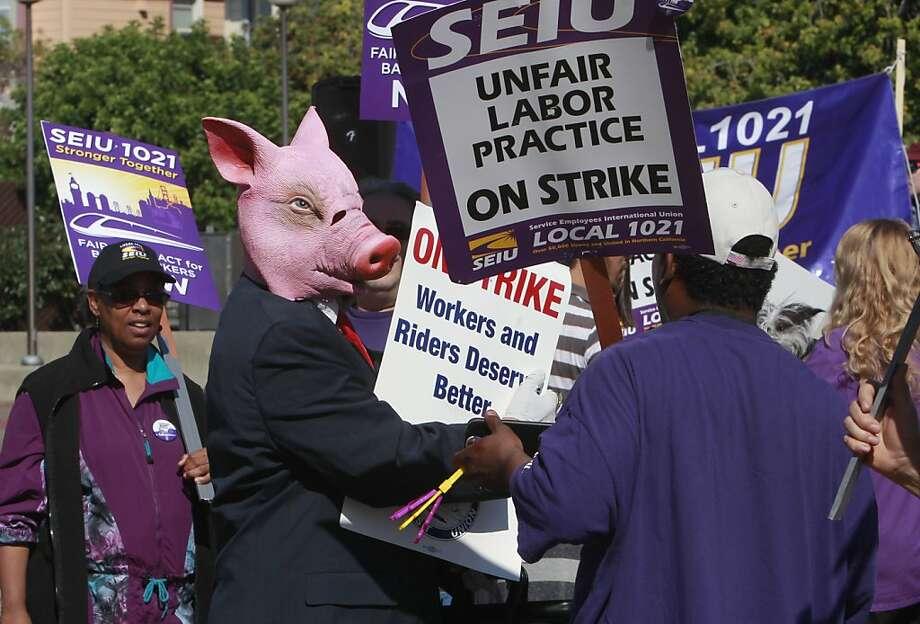 A man in a pig mask mocks BART management during a rally at the Lake Merritt BART Station. Photo: Michael Macor, The Chronicle