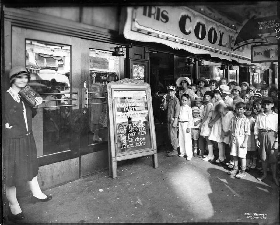 "In the '60s, people also tried to escape Houston's hot summers. Pictured are children lining up at downtown Houston's air conditioned Iris Theater for a summer ""Vacation Day Party.""  The sign promises ""free peanuts, free street car ride, free show for children 12 and under and ""Every seat is a cool retreat."" The Iris, located at the present site of the Chase Tower, opened in 1919 and was demolished in 1965. Photo: Cecil Thomson Studios, San Jacinto Museum Of History As / handout"