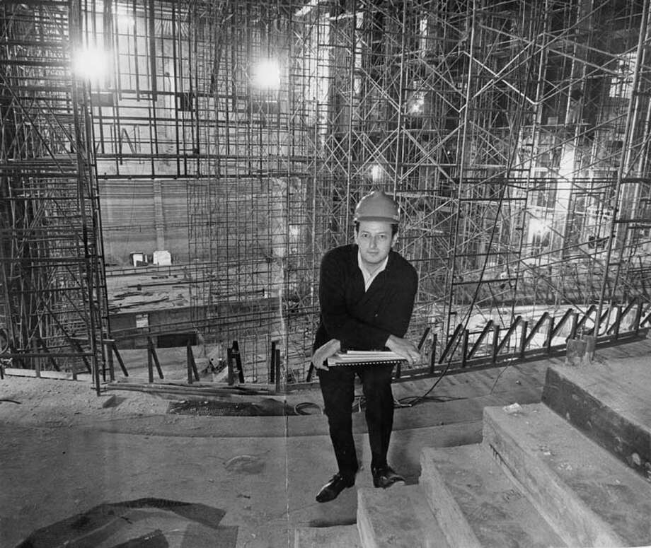 Guest conductor for the Houston Symphony season's Dollar Concert, Andre Previn, pauses for a photograph during a tour of Jones Hall following morning rehearsal, December 1965. To Previn's right, the orchestra pit and stage of the new hall are partially visible through a break in the scaffolding. Previn will conduct the Symphony in several perfomrances this season, including the Chronicle's Dollar concert, Dec. 18, 1965. Photo: Tom Colburn, Houston Chronicle / Houston Chronicle