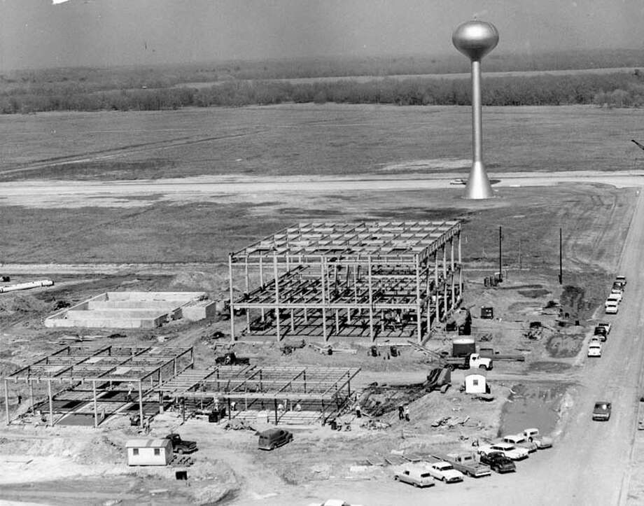 After months of expensive damage and site preparation work at the Clear Lake site of the Manned Spacecraft Center, the buildings go up in 1963. The water tower marks the center of the site which is expected to have a daily working population of 10,000 persons by the end of 1965. At left foreground is the steel framework for the firehouse. Between it and the water tower is the framework for the central heating and cooling plant. The foundation for the cooling tower may be seen near the plant structure. Photo: Owen Johnson, Houston Chronicle / Houston Chronicle