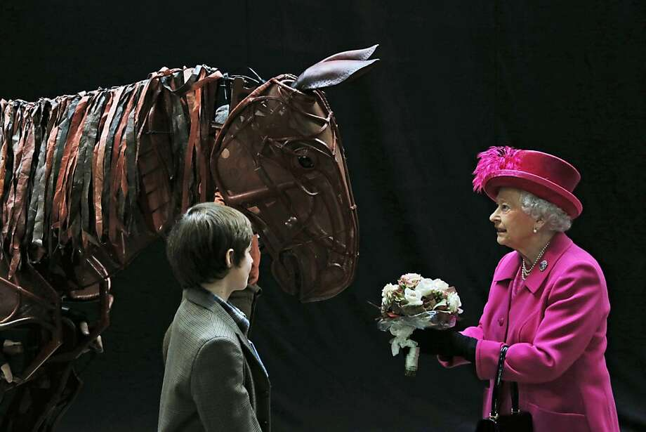Care for a bite?Queen Elizabeth II receives a bouquet from a child actor as she inspects a horse prop 