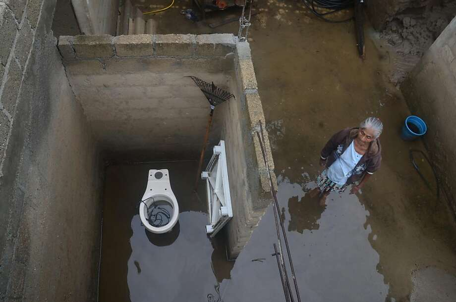 Not again:A woman stands in floodwaters from Hurricane Raymond in her damaged home in the Papa Gallo de Tierra Colorada neighborhood near Acapulco, Mexico. The house was previously flooded by Tropical Storm Manuel last month. Photo: Bernandino Hernandez, Associated Press