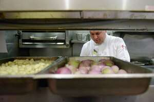 Executive Chef Joe Lucci prepares an order at Market Place Kitchen & Bar in Danbury, Conn. on Wednesday, Oct. 23, 2013.  The restaurant industry has been near the top of the list of businesses that have hired the most employees in recent years and expect to hire the most in the future.