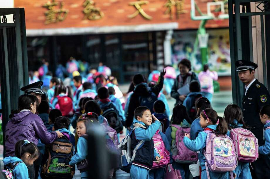 Children are dropped off at a primary school in Beijing, Oct. 19, 2012. For Chinese children and parents, education has long been seen as the key to getting ahead in a highly competitive society. Photo: SIM CHI YIN, New York Times / NYTNS