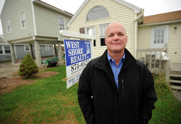 Realtor Mike Tarantino stands outside one of his Sandy damaged listings on James Street in Milford, Conn. on Wednesday, October 23, 2013. The owner had just completed repairing damage from 2011's Irene when Sandy hit. Photo: Brian A. Pounds / Connecticut Post