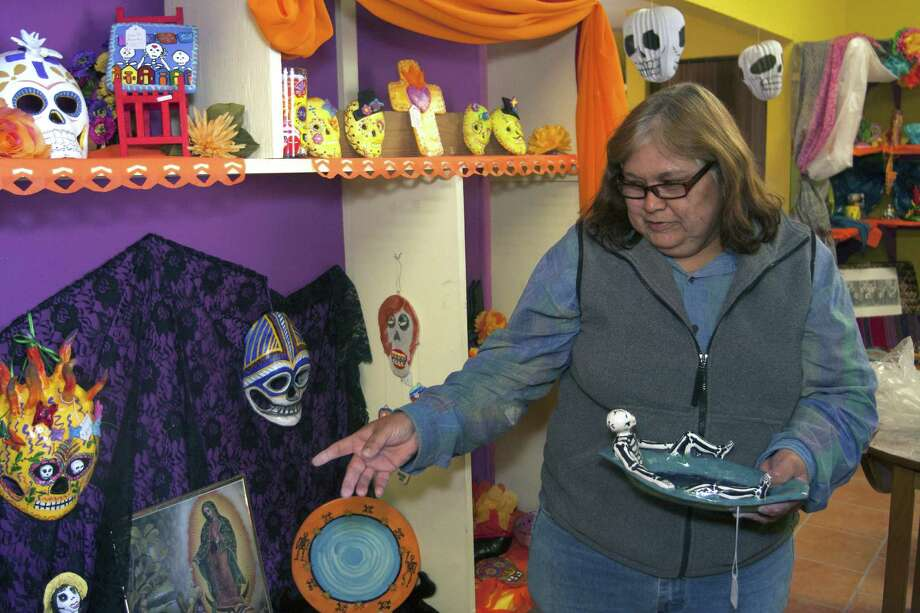 Rocky Garcia shows some of the artwork she created at Cooperativa Mujer-Artes, 1412 El Paso, with a Día de los Muertos (Day of the Dead) theme. The exhibit and sale of art by Latina women in the barrio continues through Oct. 30. Photo: San Antonio Express-News