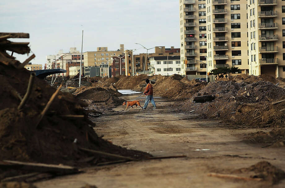 A man walks a dog through a heavily damaged sesction on November 2, 2012 in the Rockway neighborhood of the Queens borough of New York City. Photo: Spencer Platt, Getty Images / 2013 Getty Images