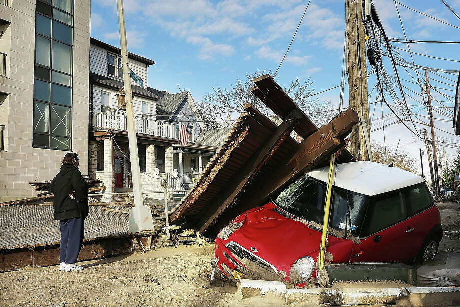 A woman looks at a damaged car, after Hurricane Sandy October 31, 2012 in the Queens borough of the Queens borough of New York City. Photo: Spencer Platt, Getty Images / 2013 Getty Images