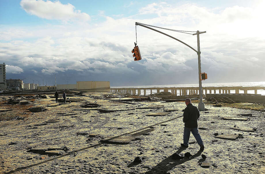 A man walks by the remains of part of the historic boardwalk, after large parts of it were washed away during Hurricane Sandy on October 31, 2012 in the Rockaway neighborhood of the Queens borough of New York City. Photo: Spencer Platt, Getty Images / 2013 Getty Images