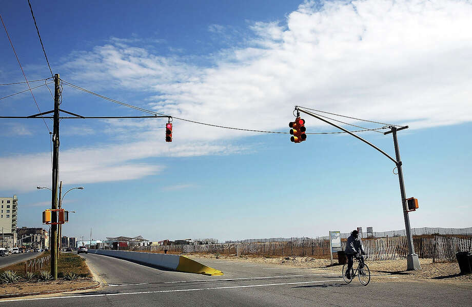 A person rides a bike October 23, 2013, in the Rockaway neighborhood of the Queens borough of New York City. Hurricane Sandy made landfall on October 29, 2012 near Brigantine, New Jersey and affected 24 states from Florida to Maine and cost the country an estimated $65 billion. Photo: Spencer Platt, Getty Images / 2013 Getty Images