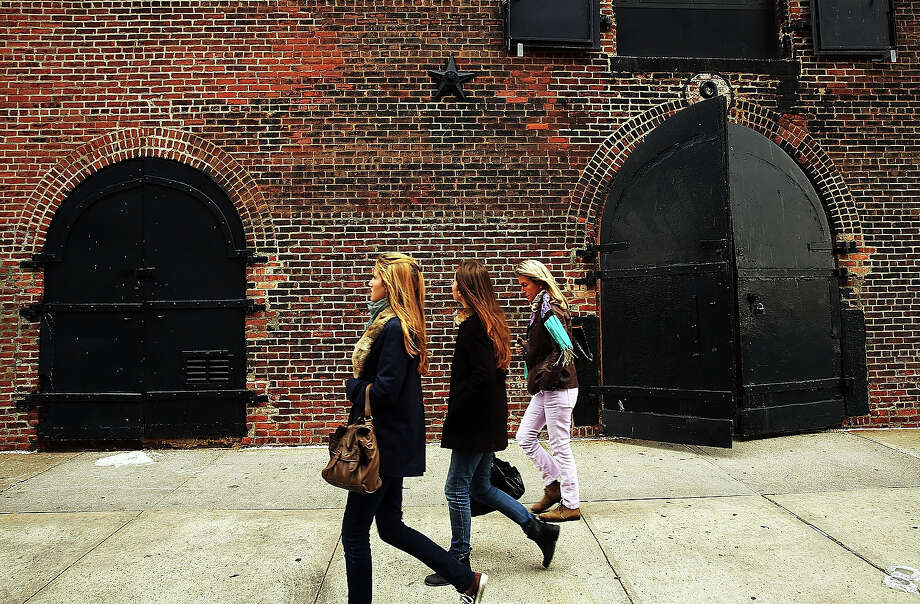 People walk past a building on October 23, 2013 in the Red Hook section of the Brooklyn borough of New York City. Hurricane Sandy made landfall on October 29, 2012 near Brigantine, New Jersey and affected 24 states from Florida to Maine and cost the country an estimated $65 billion. Photo: Spencer Platt, Getty Images / 2013 Getty Images