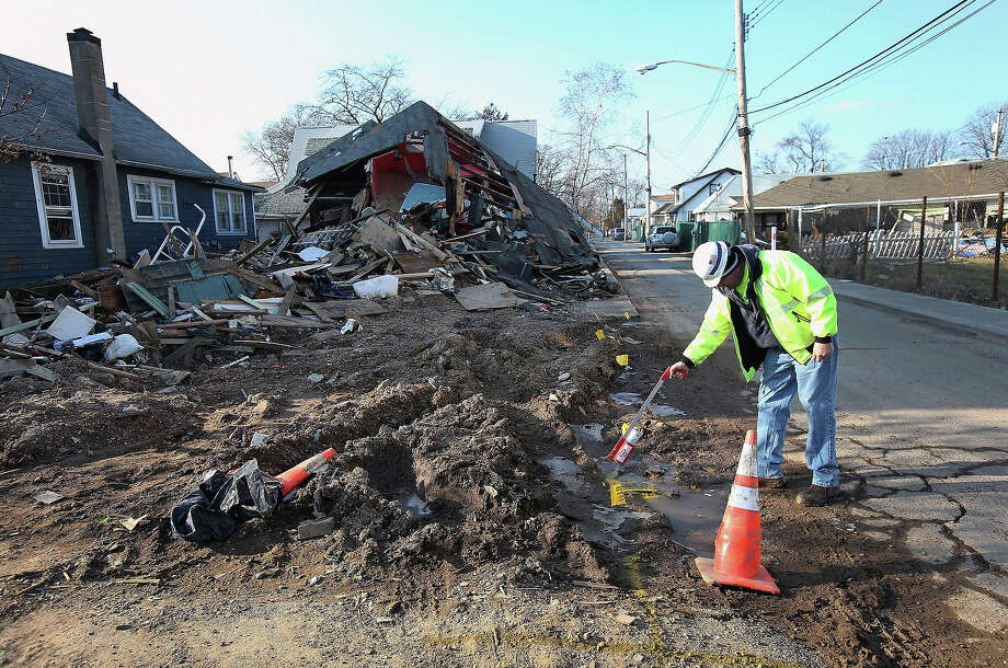 A gas worker marks a gas line in front of homes damaged by Superstorm Sandy on January 4, 2013 in the New Dorp area of the Staten Island borough of New York City. Photo: John Moore, Getty Images / 2013 Getty Images