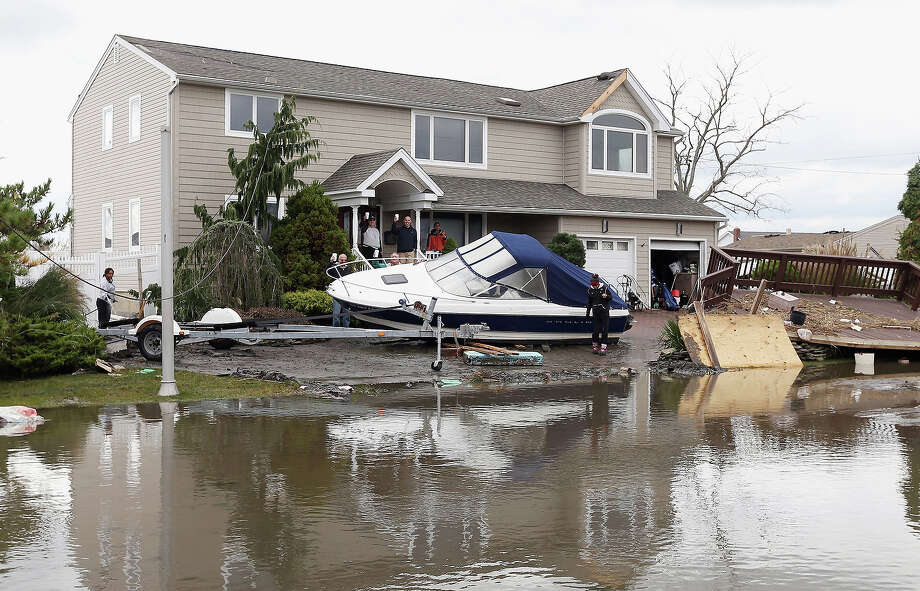 Residents of West Lido Boulevard take a break during cleanup operations following Hurricane Sandy on October 31, 2012 in Lindenhurst, New York. The storm has claimed many lives in the United States and has caused massive flooding across much of the Atlantic seaboard. Photo: Bruce Bennett, Getty Images / 2013 Getty Images