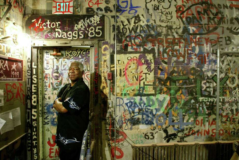 This graffitied wall behind Garfield's old auditorium had the signatures of drama students and others over the years. It was torn down for the school's remodel that started in 2006 and turned into wallpaper. Robert Stephens Jr., a 1965 Garfield grad, is pictured in front of the wall.  Photo: Dan DeLong, P-I File