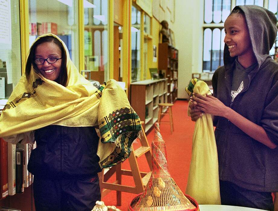 "Zanash Gebre, 18, left, is pictured in 2001 with Kidest Melaku,18, right, in the Garfield High School library. They were preparing clothes for a project called ""Voices of Fear and Change,"" which promoted tolerance and understanding of different cultures and religions.  Photo: RENEE C. BYER, P-I File"