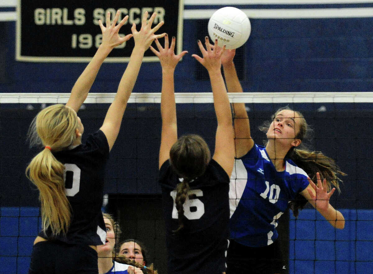 Fairfield Ludlowe's April Cooke attempts to spike the ball past Staples players Amelia Brackett, left, and Mikaela O'Kelly, during girls high school volleyball action in Westport, Conn. on Wednesday October 23, 2013.