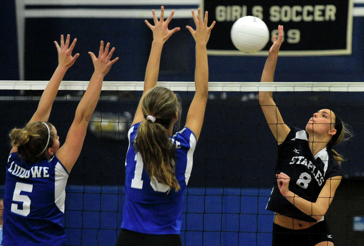 Staples Knox Schieffelin attempts to get the ball past Fairfield Ludlowe players Lauren Schreiber, left, and April Cooke, during girls high school volleyball action in Westport, Conn. on Wednesday October 23, 2013.