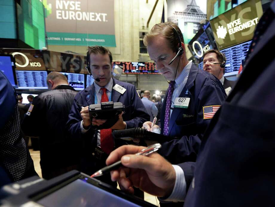 Traders Gregory Rowe, left, and Michael Smyth, center, work on the floor of the New York Stock Exchange Tuesday, Oct. 22, 2013. Stocks gained in early trading Tuesday as investors bet that the Federal Reserve would keep up its economic stimulus for longer after the government reported a slowdown in hiring last month. (AP Photo/Richard Drew) ORG XMIT: NYRD108 Photo: Richard Drew / AP