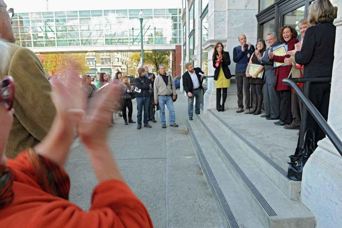 People clap during a ribbon cutting ceremony for three new stores in the landmark Troy Frear's Cash Bazaar building on Wednesday, Oct. 23, 2013, in Troy, N.Y. The new stores are E Ko Logic, Trojan Horse Antiques and Modern on the Hudson. (Lori Van Buren / Times Union)