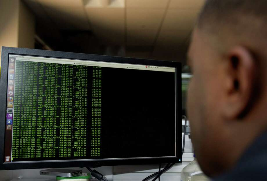 Alert Logic network security analyst Yohance Clark looks for security threats inside the company's security operations center. The company manages online threats for different entities. Photo: Cody Duty / Houston Chronicle