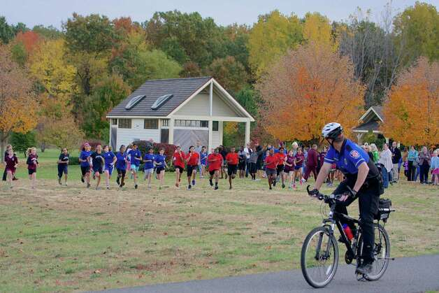 Colonie Bike Patrol Officer Sean McGee checks over his shoulder as he leads off the seventh and eighth-grade girls at the start of The Friendship League's 1-mile cross-country race on Oct. 16 at The Crossings. McGee biked the course four times, each time having to go faster to keep ahead of the increasing speed of the kids. The Friendship League is made up of Albany Community Charter School, Brown School, Doane Stuart, Hebrew Academy, Holy Spirit, KIPP Tech Valley, Menands Elementary, Parker School,  All Saints Catholic Academy, St. Gregory's, St. Pius X, and Woodland Hill Montessori. (Lise Hafner)