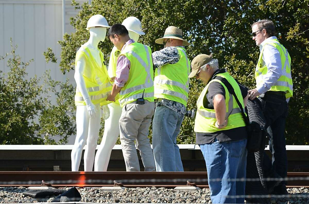 Investigators from BART and the National Transportation Safety Board use mannequins during a re-enactment of Saturday's accident that killed two workers, Wednesday, Oct. 23, 2013 in Walnut Creek, Calif. NTSB investigators conducted the re-enactment and a sight/distance study to gather more details of the incident. (AP Photo/The Contra Costa Times, Doug Duran)
