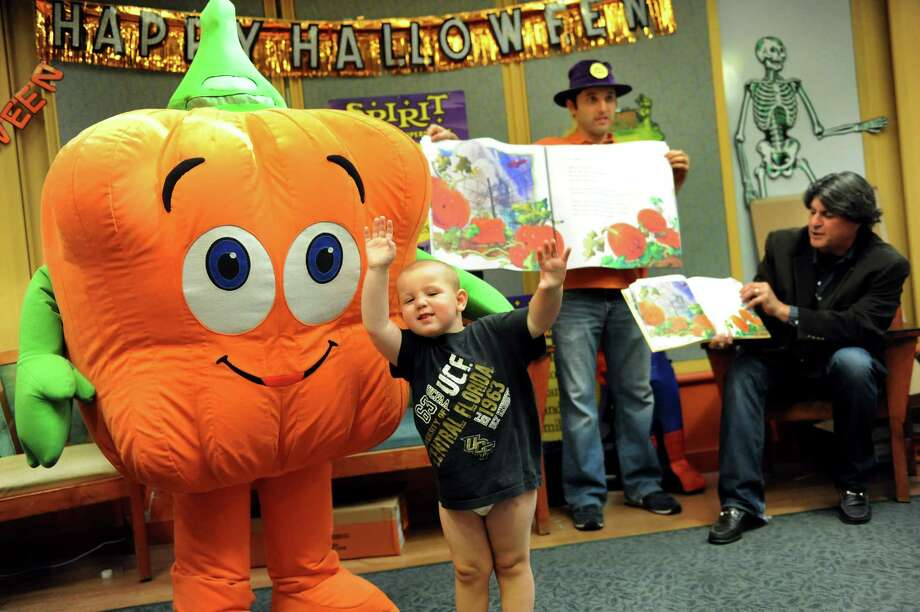 "Logan Aldrich, 3, of Albany, center, steals the show as he joins a storytelling session about Spookley, left, during a Halloween party for young patients and their families on Wednesday, Oct. 23, 2013, at Albany Medical Center in Albany, N.Y. Author Joe Troiano, right, reads ""The Legend of Spookley the Square Pumpkin"" as Aaron Burakoff turns the pages of an oversized book. Spirit Halloween stores put on the event with funds from their Spirit of Children program. (Cindy Schultz / Times Union) Photo: Cindy Schultz / 00024336A"