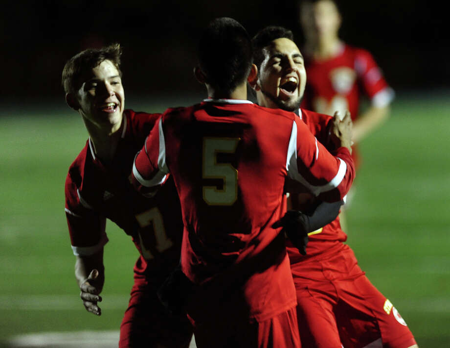 Stratford's Jairo Barrera, center, celebrates with teammates Gareth Kubic, left, and Emmanuel Silva, right, after Barrera scores against Bunnell, during boys high school soccer action in Stratford, Conn. on Wednesday October 23, 2013. Photo: Christian Abraham / Connecticut Post