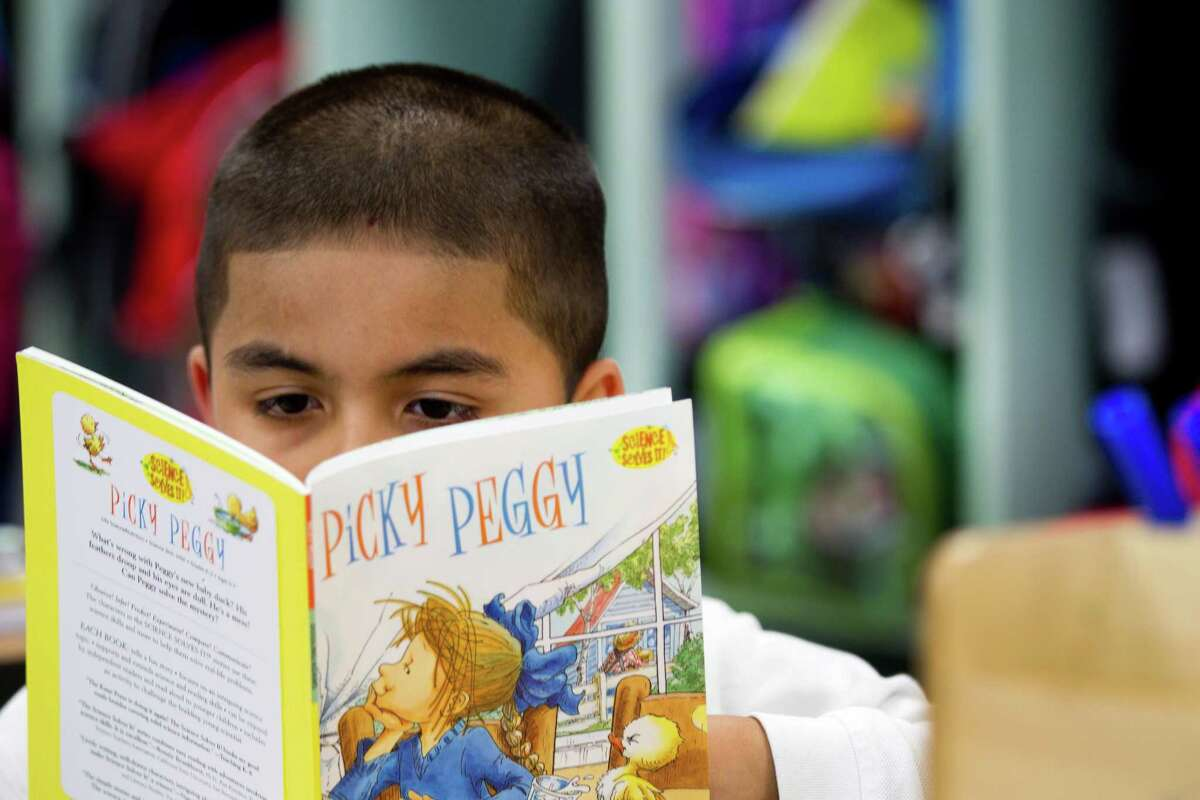 Javier Caldera reads a book at Robinson Elementary School Wednesday, Oct. 23, 2013, in Houston. A new study shows elementary schools in the Apollo program had the biggest gains, with the results better in math than in reading. The program includes small group tutoring in math.