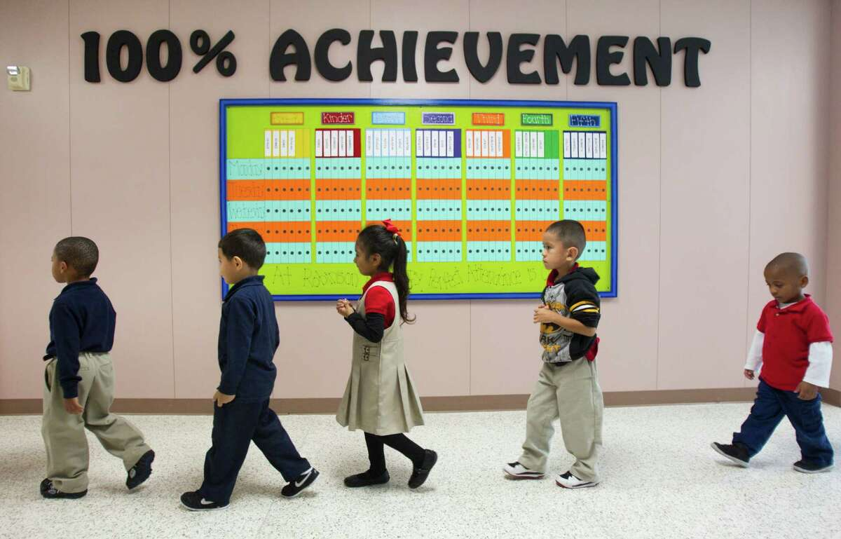 Pre-K students at Robinson Elementary School walks down the hallway Wednesday, Oct. 23, 2013, in Houston. A new study shows elementary schools in the Apollo program had the biggest gains, with the results better in math than in reading. The program includes small group tutoring in math.