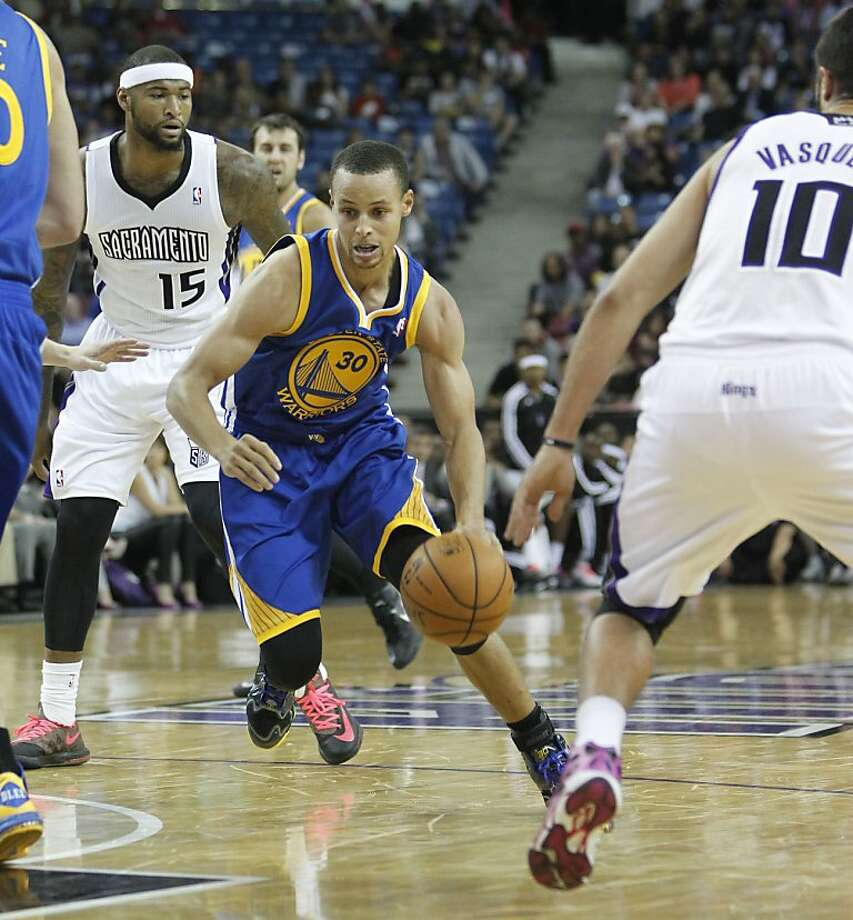 Stephen Curry, evading DeMarcus Cousins, had a game-high 24 points. Photo: Rich Pedroncelli, Associated Press