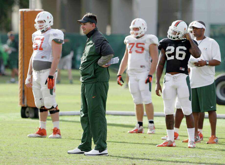 Miami head coach Al Golden, second from left, watches a drill during team practice, Tuesday, Oct. 22, 2013, in Coral Gables, Fla. Miami's football team will lose nine scholarships and the men's basketball team will lose three, as part of the penalties the school was handed Tuesday by the NCAA as the Nevin Shapiro scandal presumably drew to a close. (AP Photo/Wilfredo Lee) ORG XMIT: FLWL101 Photo: Wilfredo Lee / AP