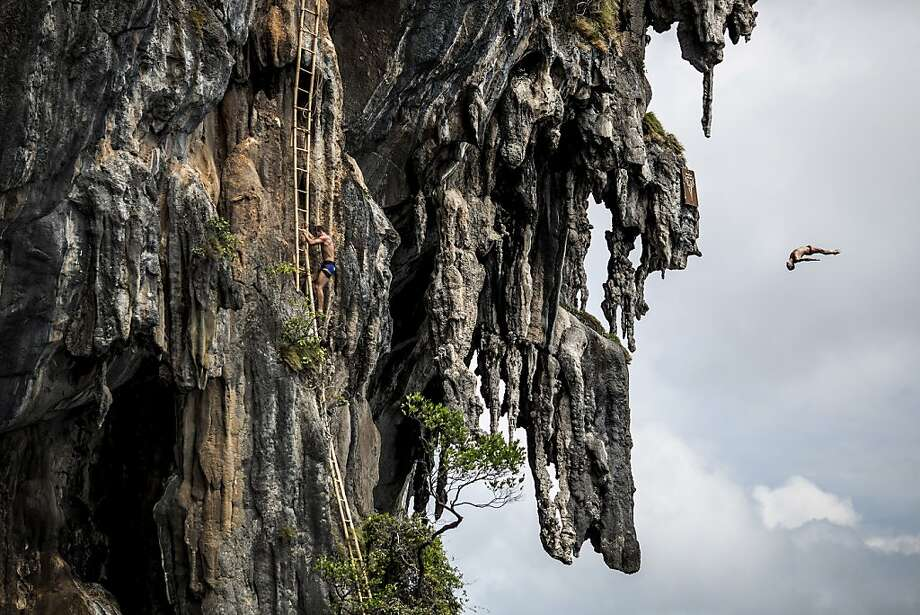 In this handout image provided by Red Bull, Blake Aldridge (R) of the UK dives from a 25 metre rock at Viking Caves in the Andaman Sea as Michal Navratil (C) of the Czech Republic makes his way up the ladders during competition on the fifth day of the final stop of the 2013 Red Bull Cliff Diving World Series on October 24, 2013 at Phi Phi Island, Thailand. Photo: Handout, Red Bull Via Getty Images