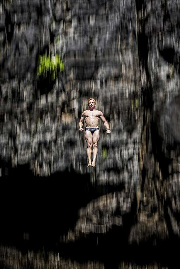 In this handout image provided by Red Bull, Alain Kohl of Luxembourg dives from the 27 metre platform at Maya Bay in the Andaman Sea during the final stop of the 2013 Red Bull Cliff Diving World Series on October 22, 2013 at Phi Phi Island, Thailand. Photo: Handout, Red Bull Via Getty Images
