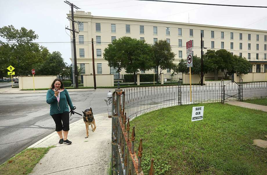 """Charlotte Luongo walks her dog """"Sirius"""" along E. Arsenal St. near the H-E-B Arsenal Headquarters, Friday, Oct. 18, 2013. Luongo lives just a block from the headquarters of H-E-B and is against plans to close S. Main in front of the compound. Photo: BOB OWEN, San Antonio Express-News / © 2012 San Antonio Express-News"""