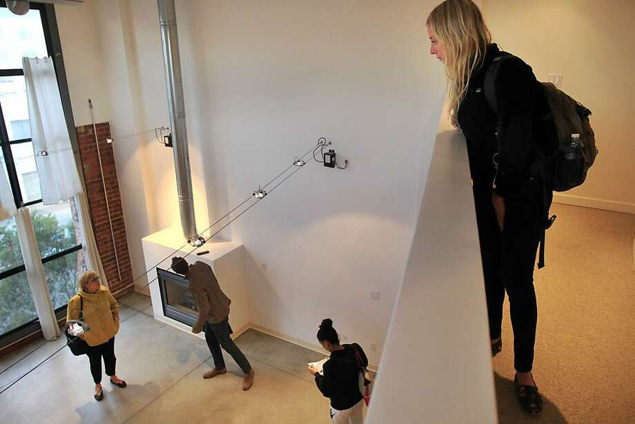 Leah Volger listens from above as real estate agent Jeanne Zimmerman (left) discusses details of a $3,800 one-bedroom, two-bath loft South of Market with Seth and Maria Skiles. Photo: Leah Millis, The Chronicle