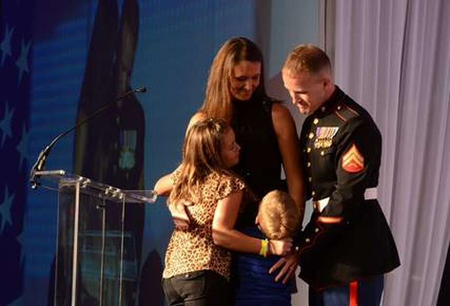 Donny Daughenbaugh hugs his wife, Sarah; daughter Gabrielle, and son Kollin at the 2012 Chicago Dinner for the Gravely Wounded.
