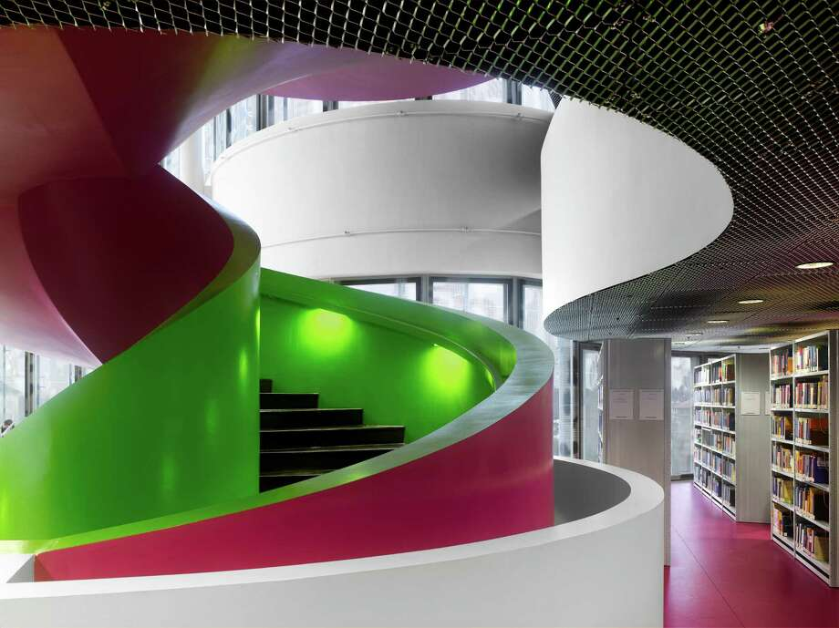 "Communications and Media Centre, BTU Cottbus, 2004. Cottbus, Germany. The floors are connected by lifts and fire-escape stairs in brightly colored circular concrete spiral staircase that twists its way through a series of one- and two-story study spaces.From ""The Library: A World History"" by Cambridge University architectural historian James Campbell and photographer Will Pryce. Photo: Will Pryce / This picture can only be used with prior permission and/or agreement of fees with Will Pryce."