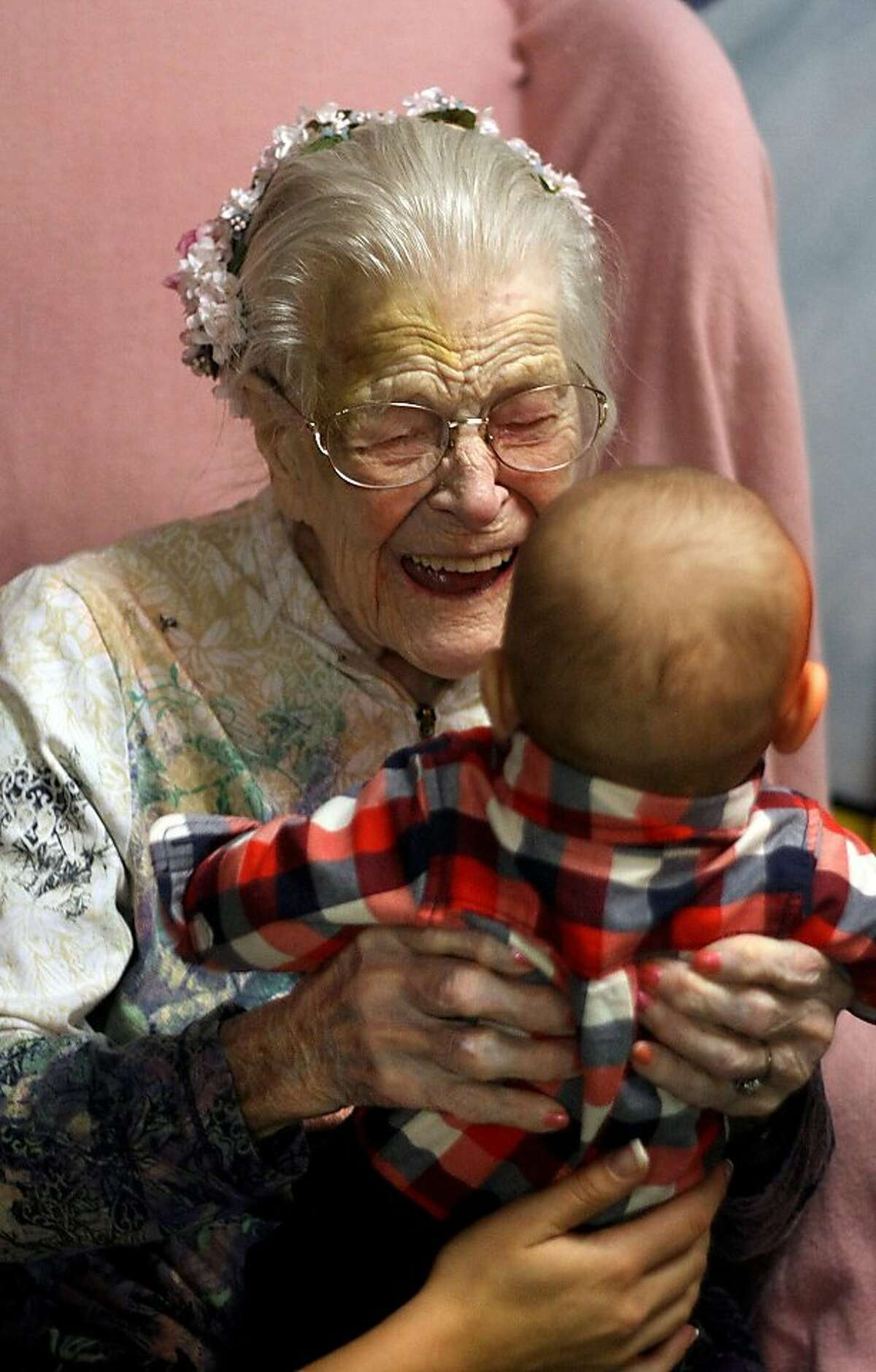 Across five generations: Emma Otis, who turned 112 Tuesday, excitedly holds her 3-month-old great-great-grandson Caleb Bennett for the first time in Poulsbo, Wash.