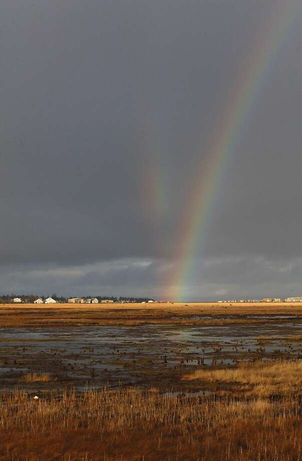 A rainbow arcs over the Kenai River flats before splitting into two in Kenai, Alaska. Photo: Rashah McChesney, Associated Press