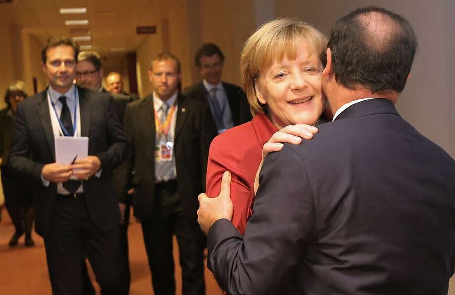 The next time you phone me, Francois, remember our nosy American friend may be listening ...German   Chancellor Angela Merkel speaks with French President Francois Hollande prior to a bilateral meeting on the   sidelines of the EU summit in Brussels. Photo: Michel Euler, Associated Press