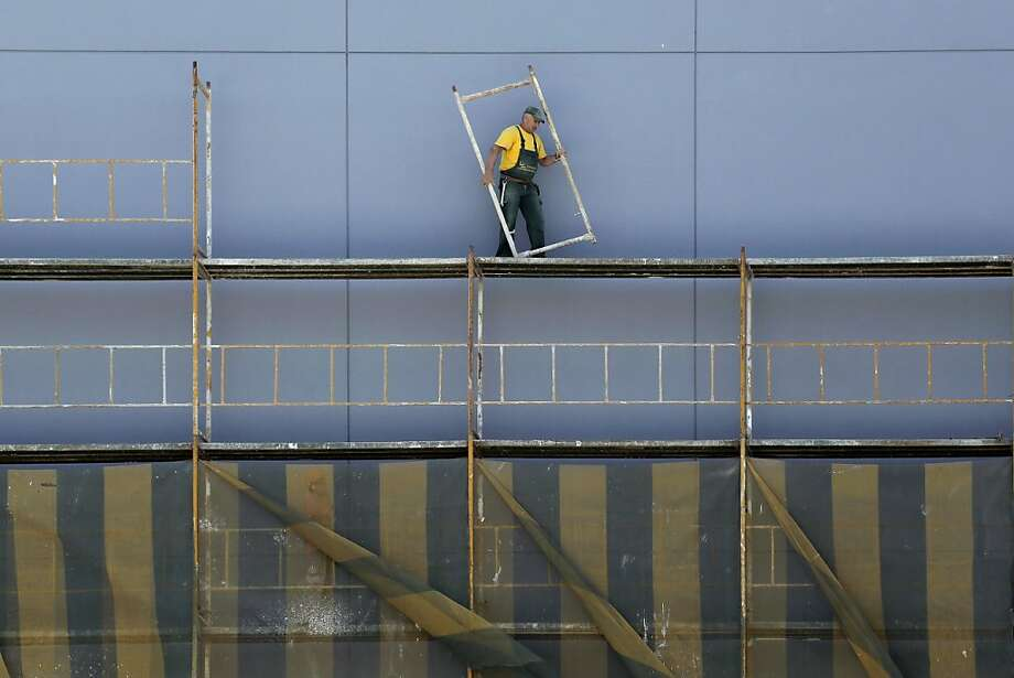Frame job: A construction laborer works on a scaffolding in central Athens. Photo: Petros Giannakouris, Associated Press
