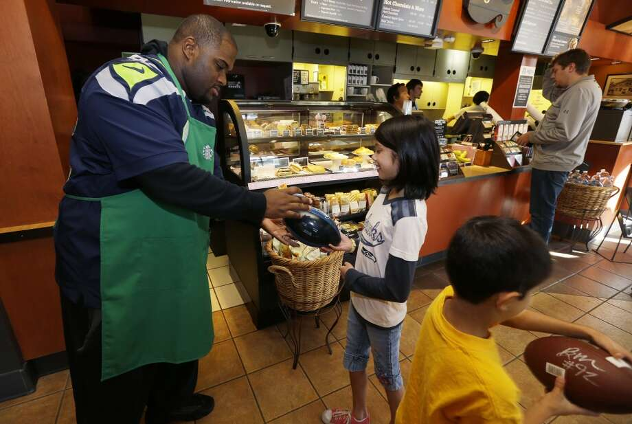 Seahawks defensive tackle Brandon Mebane signs footballs for young fans Myhanh Wong, 11, center, and brother Tai Wong, 7, right, at a Seattle Starbucks store Wednesday. Photo: Ted S. Warren, Associated Press