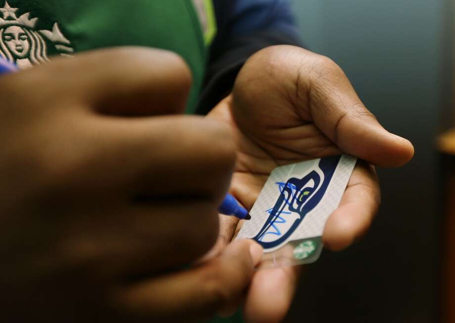 Mebane autographs a special Seahawks Starbucks card on Wednesday in Seattle. Photo: Ted S. Warren, Associated Press