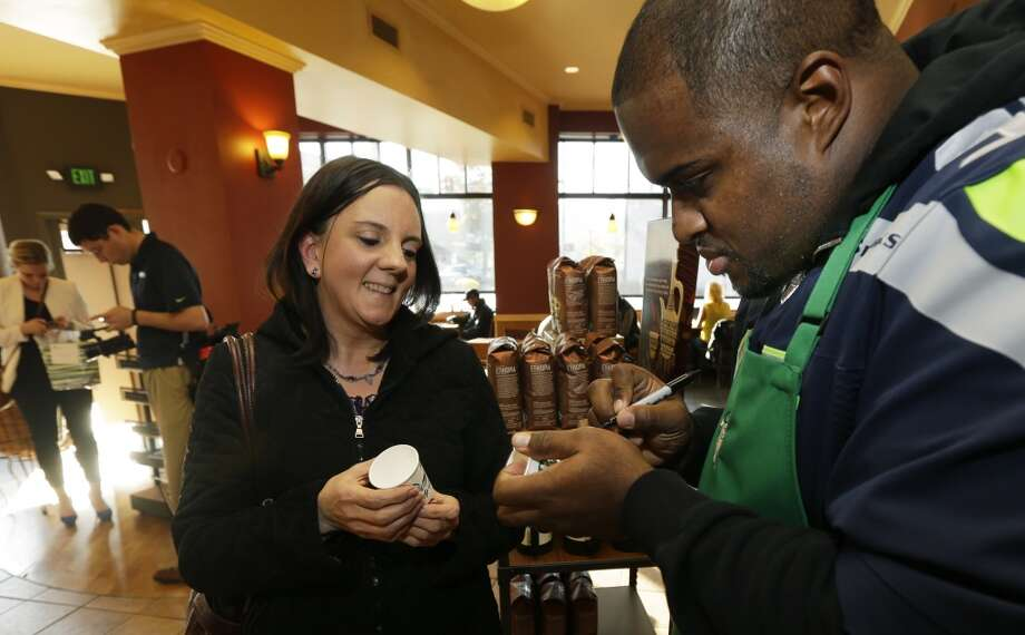 Mebane, right, autographs a Starbucks paper cup for fan Diana Crosby at a Seattle Starbucks store on Wednesday. Photo: Ted S. Warren, Associated Press