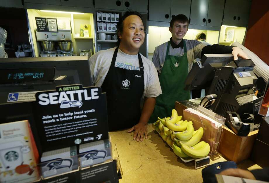 Baristas Truong Nguyen, left, and Ben Ruthruff, right, talk with customers near a display of special Seahawks Starbucks cards on Wednesday at a Seattle-area Starbucks. Photo: Ted S. Warren, Associated Press
